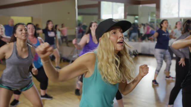 Medium panning shot of students dancing in exercise class / Orem, Utah, United States