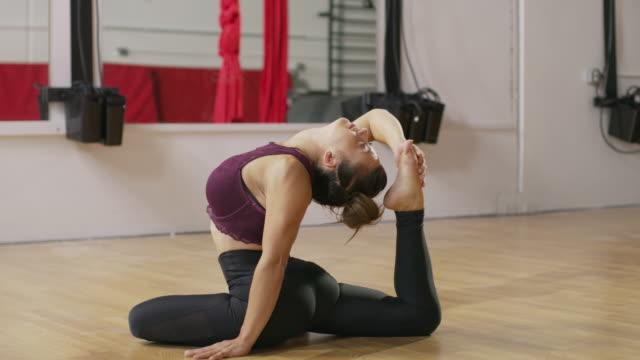 Medium panning shot of woman arching back and stretching leg / Midvale, Utah, United States