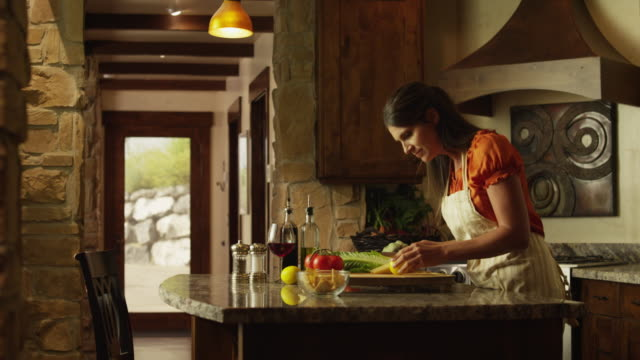 Medium panning shot of woman cooking in kitchen / Cedar Hills, Utah, United States
