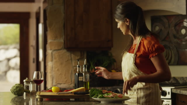 medium panning shot of woman drizzling olive oil and vinegar over salad / cedar hills, utah, united states - olive oil stock videos & royalty-free footage