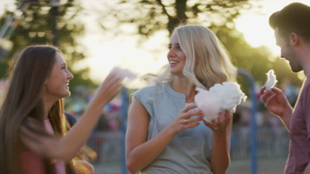 Medium panning shot of woman grabbing cotton candy from friend / Pleasant Grove, Utah, United States