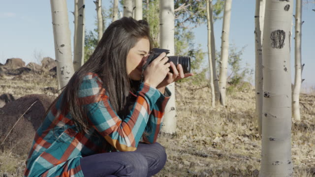 medium panning shot of woman photographing with camera in woods / boulder, utah, united states - しゃがむ点の映像素材/bロール