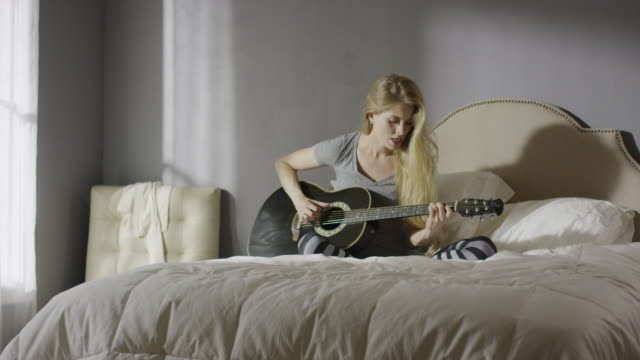vidéos et rushes de medium panning shot of woman playing guitar and singing in bed / cedar hills, utah, united states - cheveux blonds