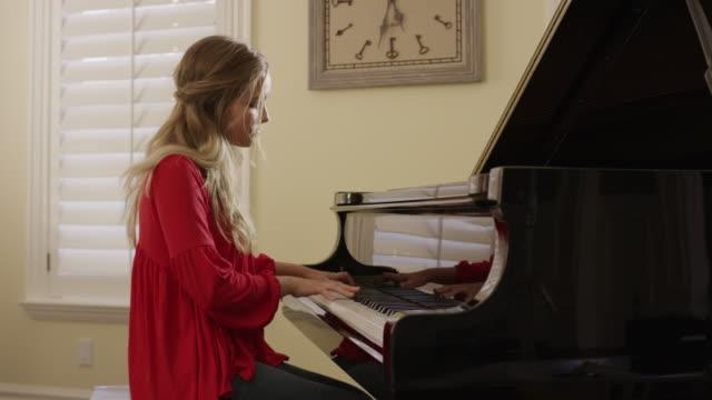 medium panning shot of woman playing piano / cedar hills, utah, united states - donne giovani video stock e b–roll