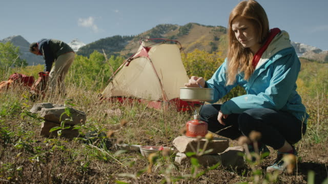 medium panning shot of woman stirring pot on camping stove / american fork canyon, utah, united states - american fork canyon bildbanksvideor och videomaterial från bakom kulisserna