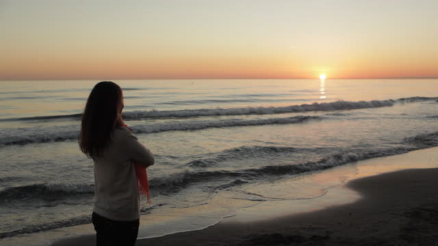 medium panning shot of woman walking on beach/marbella region, spain - one mid adult woman only stock videos & royalty-free footage