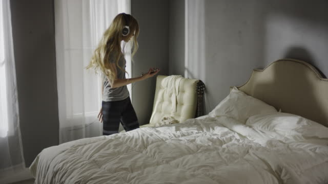 Medium panning shot of woman with headphones dancing in bedroom / Cedar Hills, Utah, United States