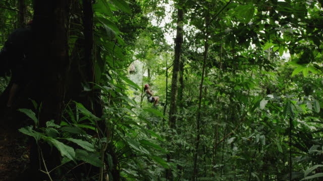 medium panning shot of woman ziplining to landing in rain forest / quepos, puntarenas, costa rica - ロープスライダー点の映像素材/bロール