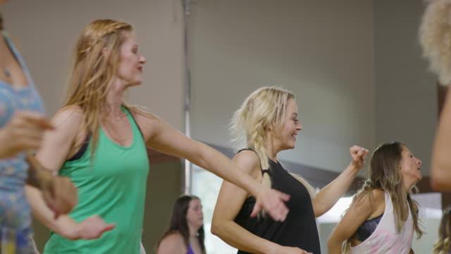 medium panning shot of women dancing in exercise class / orem, utah, united states - trousers stock videos & royalty-free footage