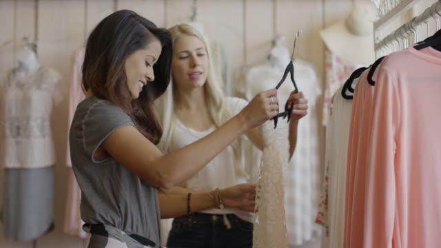 Medium panning shot of women examining skirt in clothing store / American Fork, Utah, United States