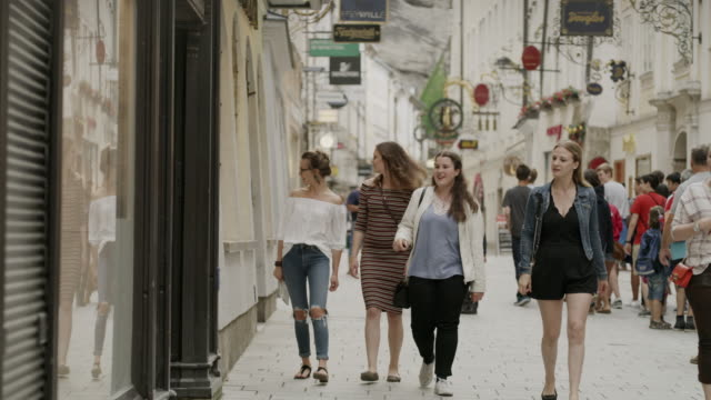 vídeos de stock, filmes e b-roll de medium panning shot of women window shopping in city / salzburg, austria - jaqueta jeans