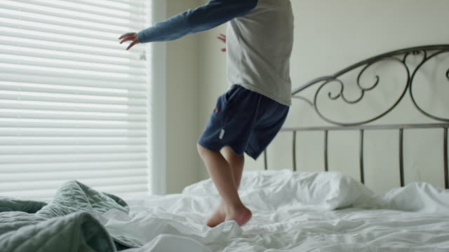 Medium panning slow motion shot of boy jumping on bed / Cedar Hills, Utah, United States