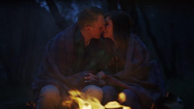 "vidéos et rushes de ""medium panning slow motion shot of couple kissing by campfire / american fork canyon, utah, united states"" - embrasser sur la bouche"