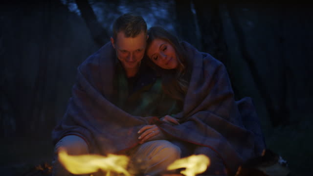 """""""Medium panning slow motion shot of couple relaxing by campfire / American Fork Canyon, Utah, United States"""""""
