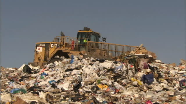 medium pan-right - a bulldozer pushes trash around a landfill / bakersfield, california - rubbish dump stock videos & royalty-free footage