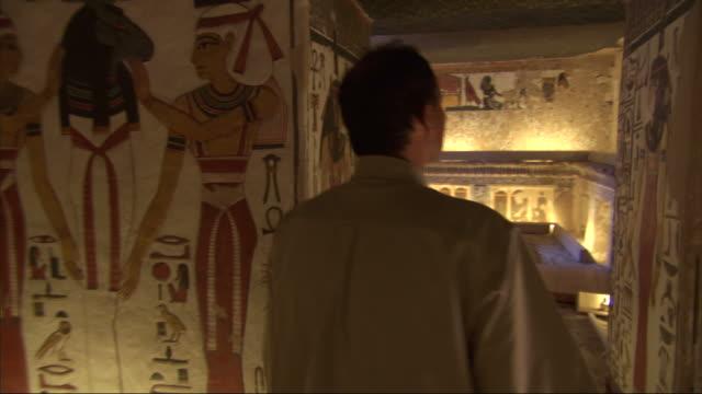 medium, pan-right - a man views murals depicting egyptian life - archäologie stock-videos und b-roll-filmmaterial