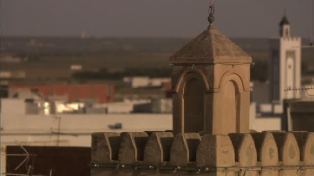 Medium LS pan-right rack-focus A flock of birds flies behind towers in Libya. / Libya