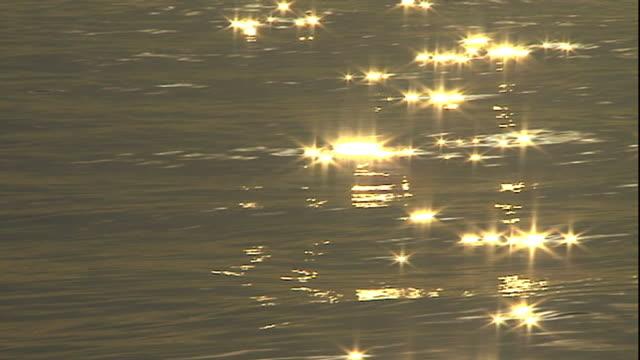 Medium pan-right tilt-up - Sunlight sparkles on the ocean.