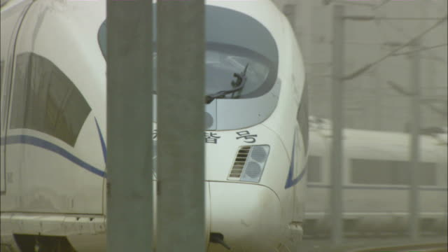 Medium pan-right zoom-out - A high speed rail train glides over the rails./Beijing, China