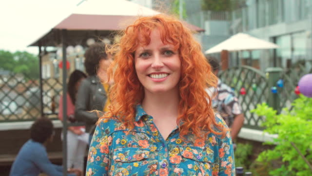 medium portrait of a young redheaded woman at a party - stile di capelli video stock e b–roll