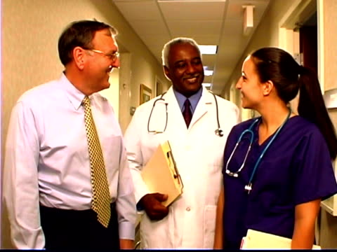 medium portrait shot of a doctor, a nurse and an administrator in a hall. - female with group of males stock videos & royalty-free footage