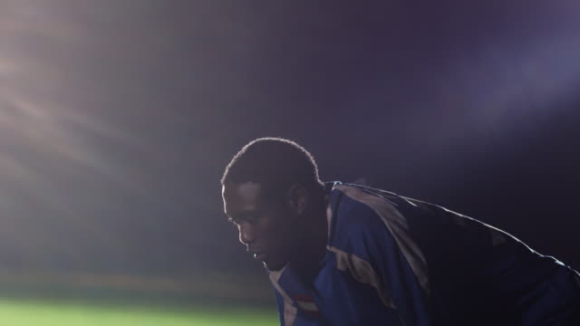 Medium profile of soccer player bent over to catch his breath on field (spotlights in background)