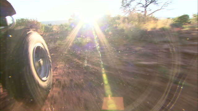 medium push-in - the sun shines over the wheel of an atv as it drives over red dirt /  - 行く手点の映像素材/bロール