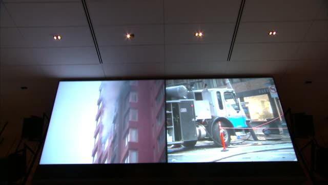 Medium push-out tilt-down - Control room surveillance screens monitor activity in New York City. / New York City, New York, USA