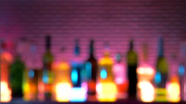 medium rack focus on a row of backlit liquor bottles on a bar. - aufblenden stock-videos und b-roll-filmmaterial