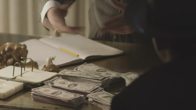 medium reenactment shot of a mob boss talking to gangsters over a pile of cash on his desk during prohibition era - organized crime stock videos & royalty-free footage