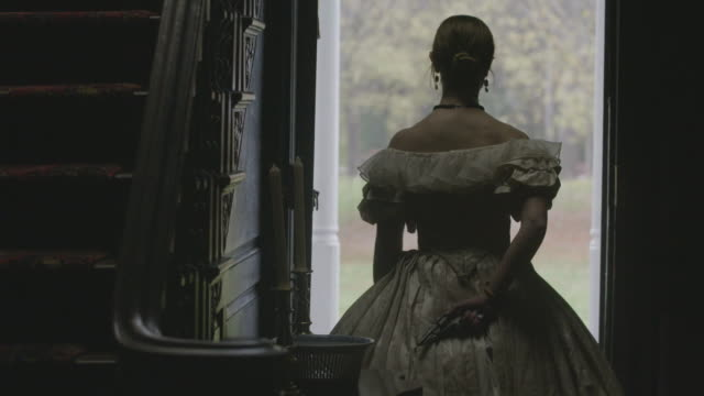 stockvideo's en b-roll-footage met medium reenactment shot of a woman in costume holding a gun behind her back while standing at the entrance of a historical mansion during the civil war era - 18e eeuwse stijl
