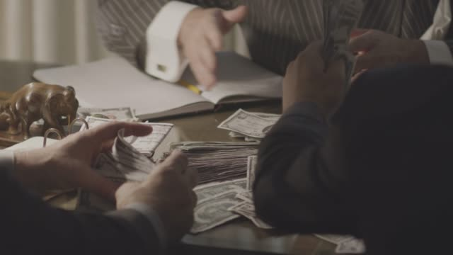 medium shot of gangsters stacking up cash on the desk of a mob boss - mafia stock videos and b-roll footage