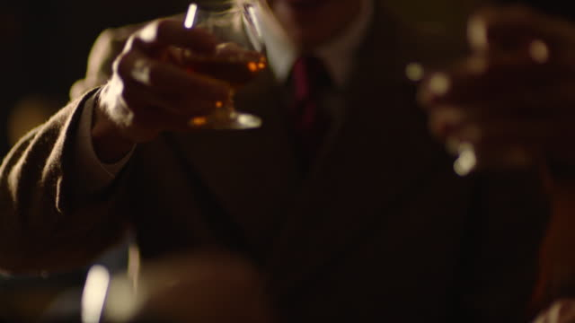 medium shot of men cheering with whiskey around the table - reenactment stock videos & royalty-free footage