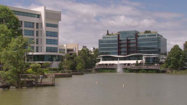 medium rise office buildings surround a man made lake with a fountain and boardwalk in the norwest business district of castle hill / main street... - straßenschild stock-videos und b-roll-filmmaterial