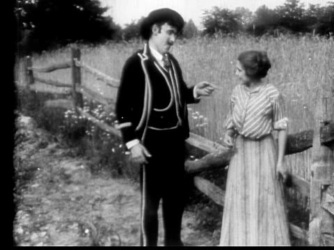 stockvideo's en b-roll-footage met 1910 b/w medium salesman flirting with maid in yard by giving her ring  - 1900 1909