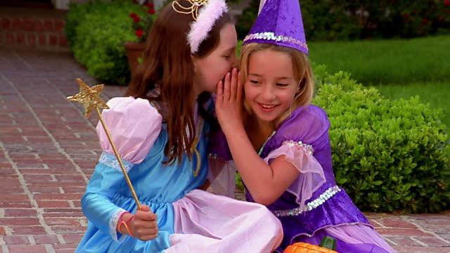 Medium shot 2 girls in Halloween costumes posing / whispering and laughing