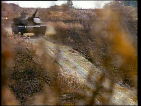 stockvideo's en b-roll-footage met medium shot 2 tanks moving down dirt road / dust cloud following / camp shelby, mississippi - onbekend geslacht