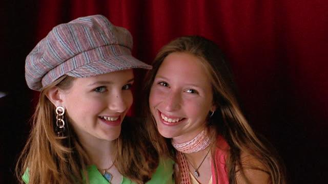 vídeos y material grabado en eventos de stock de medium shot 2 teenage girls posing / red curtain in background - sólo grupo de adolescentes
