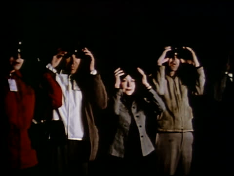 1953 medium shot 2 women and 2 men pulling goggles over eyes / loudspeaker military voice AUDIO