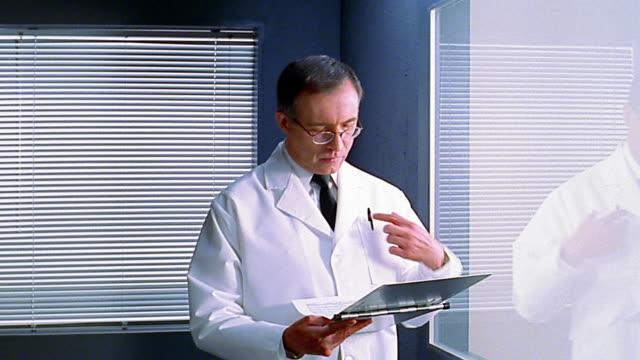 medium shot 3 doctors talking near window - クリップボード点の映像素材/bロール