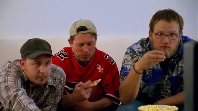 Medium shot 3 men eating pizza and snacks while watching TV