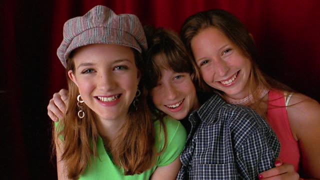 medium shot 3 teenagers posing / red curtain in background - male with group of females stock videos & royalty-free footage