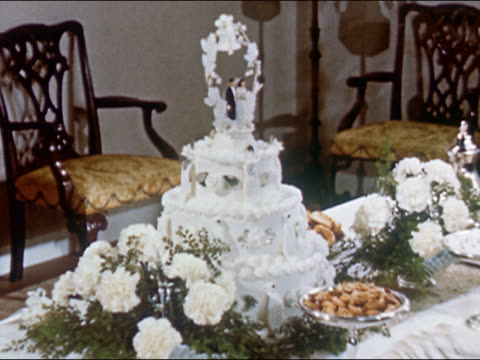 1951 medium shot 3-layer wedding cake on table surrounded by food and flowers / audio - 小さな像点の映像素材/bロール
