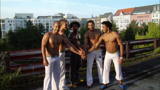 vídeos de stock, filmes e b-roll de medium shot. a group of male capoeira dancers raising their hands in unison. - posição de combate