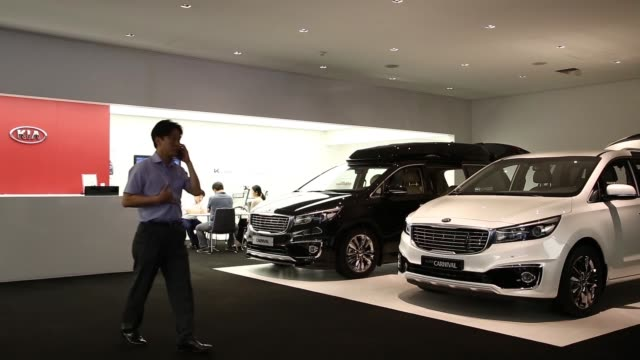 medium shot a kia motors corp carnival minivan at one of the company's dealerships in seoul wide shot an employee left speaks to customers next to a... - limousine familienfahrzeug stock-videos und b-roll-filmmaterial