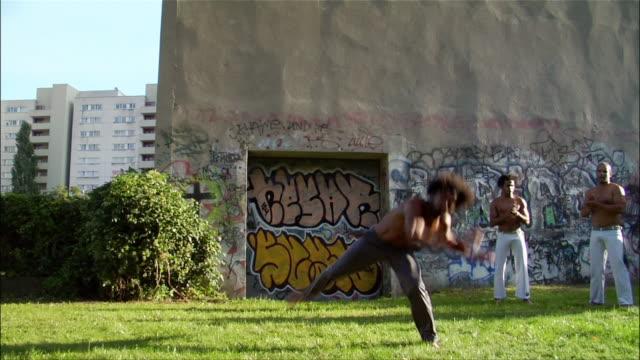 vídeos y material grabado en eventos de stock de medium shot. a male capoeira dancer performs while another man watches and claps. - masculinidad