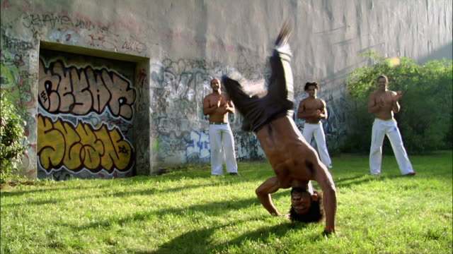medium shot. a male capoeira dancer performs while other men watch and clap. - ファイティングポーズ点の映像素材/bロール
