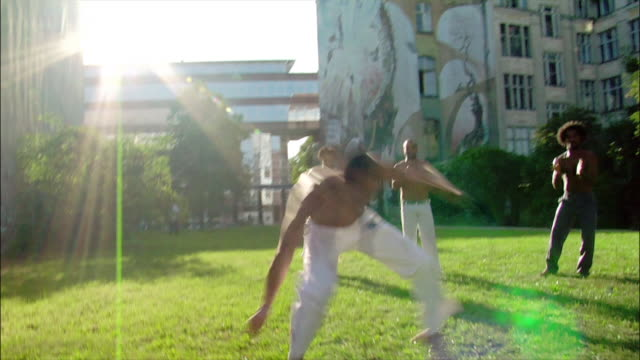 medium shot. a male capoeira dancer performs while other men watch and clap. - バク転点の映像素材/bロール