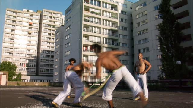 vídeos de stock, filmes e b-roll de medium shot. a male capoeira dancer performs while other men watch and clap. - posição de combate