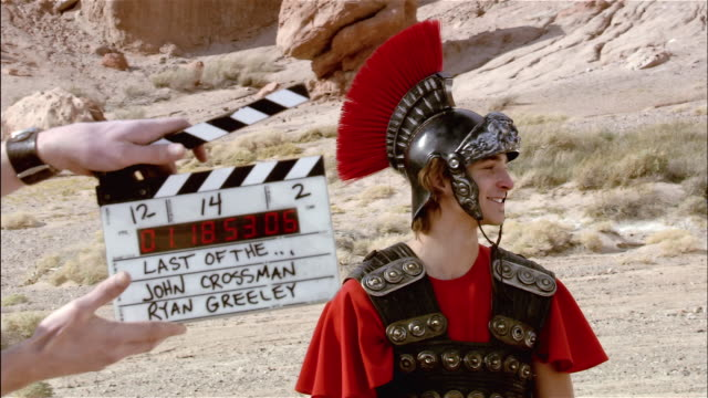 medium shot actor wearing a roman soldier costume laughing and talking / slate appearing in foreground / actor laughing and throwing hands up / red rock canyon state park, california - roman soldier stock videos and b-roll footage